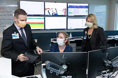 Professionals with face masks looking at computer screens
