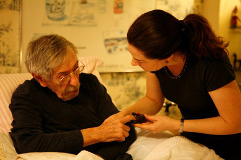 Home care nurse taking care of elderly man in bed