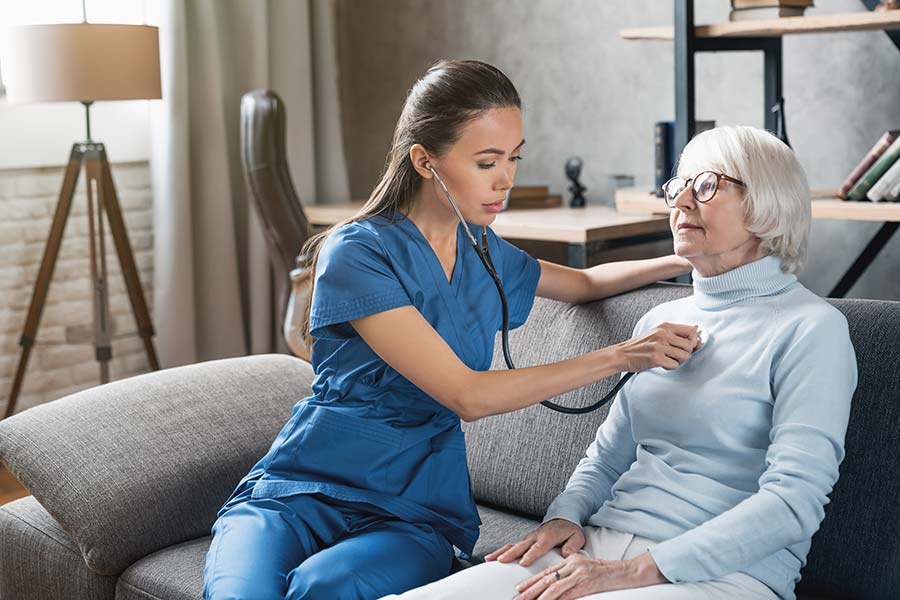 Nurse listening to a senior woman's heart